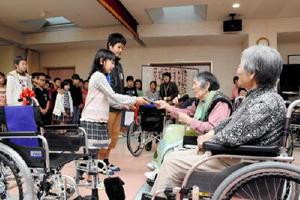 車いす寄贈のお礼として眞島ナミエさん(右から2番目)が大野ひかりさんに図書券を手渡した=佐賀市大和町の特別養護老人ホーム「ロザリオの園」