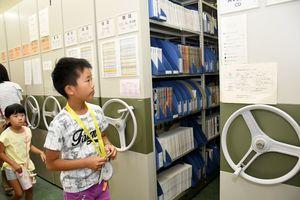 普段見ることのできない「閉架書庫」を見学する児童ら=佐賀市の市立図書館