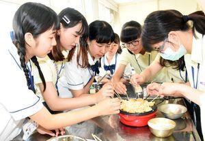顔をくっつけ合うようにして、竹串でたこ焼きをひっくり返す生徒たち。タイのない、黄色い制服が台湾の生徒たち=鳥栖商高
