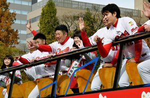 プロ野球広島カープのセ・リーグ連覇を祝うパレードで、招待された県内の女子大学生と手を振る選手ら=25日午前、広島市