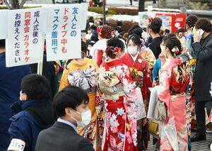 マスク姿で談笑する新成人。式典会場入り口付近では職員が新型コロナウイルスの感染防止を呼び掛けた=佐賀市文化会館(撮影・鶴澤弘樹)