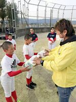 少年野球チームの子どもたちに、消毒液と噴霧器を手渡した小城市商工会青年部員=小城市牛津町(同青年部提供)