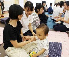 保湿剤の塗り方を教える学生(左から2人目)=佐賀市の鍋島公民館(提供)