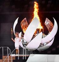 東京五輪の開会式で聖火台に点火し、トーチを掲げるテニス女子の大坂なおみ=23日夜、国立競技場