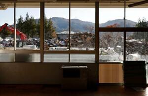宮城県丸森町立金山小の教室から見える校庭に積まれた災害ごみ=6日