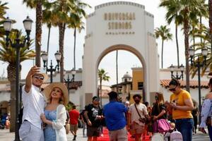 15日、米ロサンゼルスの「ユニバーサル・スタジオ・ハリウッド」で自撮りする訪問客(ロイター=共同)