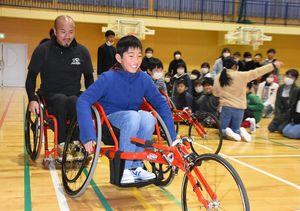 競技用車いすに試乗する佐志小の5年生。左後方が副島正純選手=唐津市の同小体育館