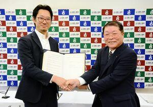 進出協定を結んだタイムカプセルの相澤謙一郎社長(左)と吉野ヶ里町の伊東健吾町長=同町役場