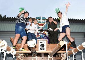 東町唐獅子会の有志と一緒に、東町の山車「唐獅子」に上がって記念写真に写るブルーノさん(右)=鳥栖市本町の八坂神社