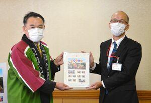 田中本部長(右)からフレーム切手を受け取る峰市長=唐津市役所