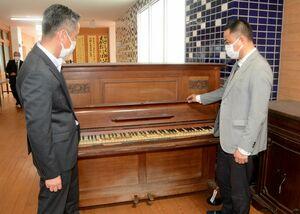 保管されている95年前のシードマイヤー製のピアノを見る西山智久委員長(右)と松本成浩校長=有田町の有田小