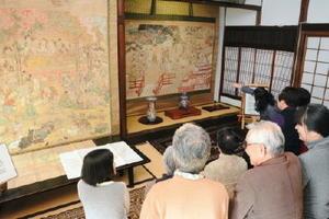 お釈迦様の誕生と最期を描いた「誕生図」と「ねはん図」に見入る来訪者たち=佐賀市唐人の城雲院