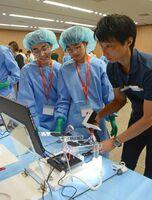 腹腔鏡手術の体験で、テレビモニターを見ながら鉗子を操作する中高生ら=佐賀市の県医療センター好生館