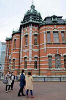 福岡市赤煉瓦文化館(旧日本生命九州支店)の外観を眺めるツアー客=福岡市中央区天神