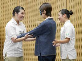 全国高校生介護技術コンテストで、「全盲の80代女性」を介助する神埼清明高の大隈沙希さん(左)と二宮花音さん(右)=新潟県(同校提供)