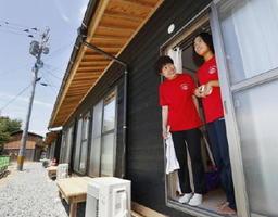 仮設住宅の中に入り、外を眺める林恵子さんと紗季さん親子=18日午後、福岡県朝倉市