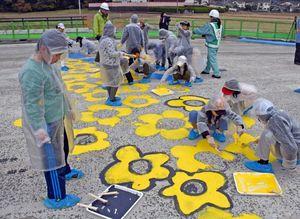 バイパスの橋のコンクリートに花びらを描く北方小の3年生=武雄市北方町