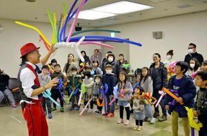 子どもたちにバルーンアートの妙技を披露するさと原人さん(左手前)=唐津市民会館
