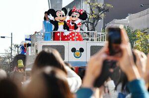 ディズニーパレードで観客に手を振るミッキーマウスとミニーマウス=2日午後、佐賀市の佐賀銀行本店前