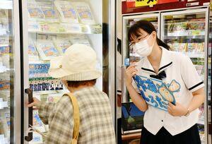 商品を手に取った買い物客に声をかける島ノ江葉月さん(右)=佐賀市のスーパーモリナガ南佐賀店