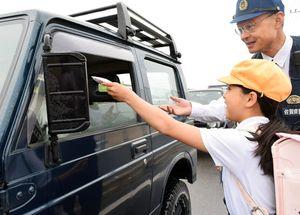 通勤中のドライバーに安全運転を呼び掛ける「ポプリ」を手渡す児童=神埼市の仁比山小正門前