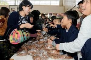 益金を熊本地震の義援金にするため育てたサツマイモを販売する五町田小4年生の子どもたち(右側)=嬉野市の五町田小学校