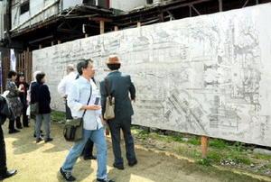 展示された「二百五十年祭禮之図」の拡大図。新馬場通りがにぎわった様子が描かれ、地元住民や歴史ファンも見入った=佐賀市の松原神社鳥居前広場