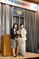 鈴木幸子ガバナー(左)から記念の盾を受け取る国際ソロプチミスト佐賀中部の真子通子会長=佐賀市のガーデンテラス佐賀