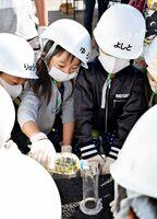 アスファルトに色水を流して排水性を確かめる児童たち=佐賀市嘉瀬町の中野建設佐賀合材工場