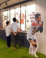五郎丸歩さんの愛用品が並ぶ特別展示。プレースキック時のポーズのパネルが来場者を出迎える=県庁地下1階の「SAGA TRACK」