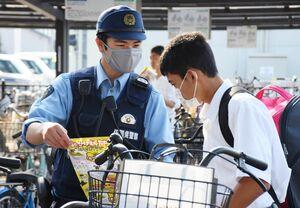 通学生にチラシを配り、自転車の施錠を呼び掛ける小城署員=小城市のJR小城駅