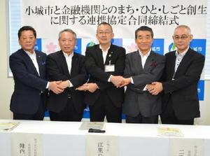 地方創生に関する連携協定を交わした江里口秀次市長(中央)と金融機関の代表=小城市役所