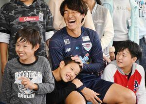 嘉瀬小の児童と交流し、笑顔を見せるサガン鳥栖の金崎夢生選手=佐賀市の同校