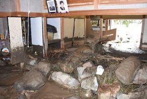 家屋の1階に土砂や大きな岩が流入して半壊した民家=7日、三養基郡基山町