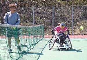 東京五輪・パラリンピック延期の一報から一夜明け、車いすテニスのトレーニングに臨む大谷桃子(右)と古賀雅博コーチ=神埼市の西九州大
