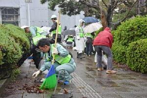 歩道に積もった落ち葉をほうきや手で集める会員たち=佐賀市の県庁前