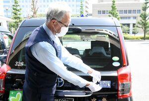 ステッカーをタクシーに貼り付ける運転手=佐賀市の県警本部