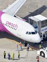 前輪のタイヤがパンクして福岡空港の滑走路で動けなくなり、駐機場にけん引されたピーチ・アビエーション機=24日午前10時39分(共同通信社ヘリから)