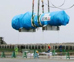 ブルーシートにくるまれて海上から搬入される、九州電力川内原発2号機の蒸気発生器=28日午前、鹿児島県薩摩川内市