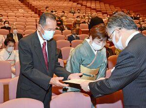 坂田勝次専務取締役(右)から表彰状を受け取る金婚さん夫婦=佐賀市文化会館