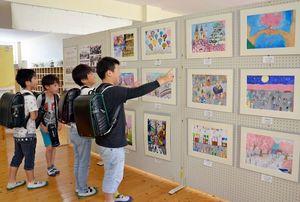 ボスニア・ヘルツェゴビナの子どもたちの入賞作品を眺める児童たち=唐津市の佐志小