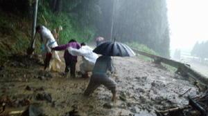 山から噴き出した泥水があふれる道を必死に歩く住民=7月5日午後6時21分、福岡県朝倉市の黒松・真竹集落(町田秀紀さん提供)