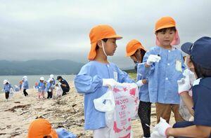 砂浜のごみ拾いをするリョーユー幼稚園の園児と唐津海上保安部の職員=唐津市の東の浜海岸