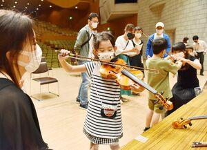 佐賀交響楽団のメンバーから指導を受け、バイオリンの演奏に挑戦する児童たち=佐賀市文化会館