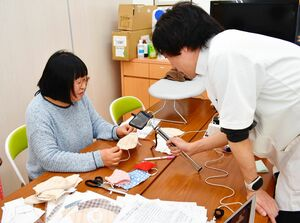テレビ会議システムを使ってマスク作りを実演する薬局職員=伊万里市新天町のカイセイ薬局