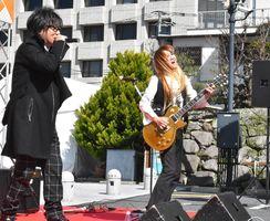 17日のサテライト館のオープニングイベントでテーマソングを初披露する高取ヒデアキさん(左)、伸和さん兄弟=唐津市本町の旧唐津銀行