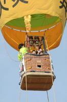 子どもたちを乗せたバルーンが約30㍍の高さまで上がり、遠くに有明海を望む景色を満喫した=鹿島市の中川グラウンド