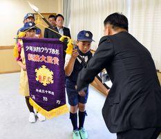 峰達郎市長から旗を受け取る堂脇雅仁さん=唐津市役所