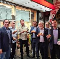 19日、米ニューヨークの路上でピザを食べるブラジルのボルソナロ大統領(左から3人目)ら(マシャド観光相のインスタグラムから、共同)