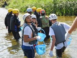 ヤマメ放流で川に入っていくクサック村の中学生たち=佐賀市三瀬村三瀬付近の嘉瀬川